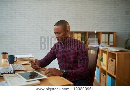 Waist-up portrait of hard-working entrepreneur dialing number of his business partner while sitting at workplace, interior of modern office on background