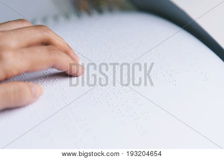 Finger read braille text in white paper.