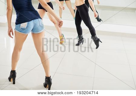 Group of young women learning dance moves with help of coach while having class in spacious hall