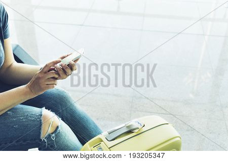 Young hipster girl at airport and put feet in yellow boot on suitcase waiting air flight female hands holding smart phone in terminal departure lounge gate traveler trip concept mockup of blank screen sellphone