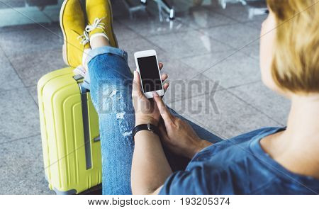 Young hipster girl sitting at airport and put feet in yellow boot on suitcase traveling in Europe female hands texting message on gadget in terminal area hall traveler journey trip concept mockup blank screen