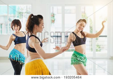 Attractive Asian women shaking their hips while performing belly dance in spacious hall with panoramic windows