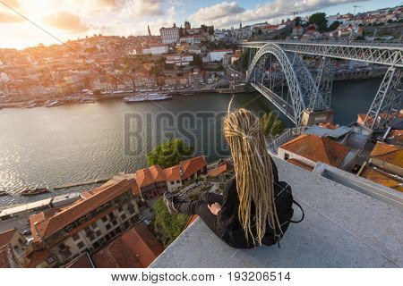 Young woman with blond dreadlocks sitting on viewpoint in front of Douro river and Dom luis I bridge in Porto, Portugal.