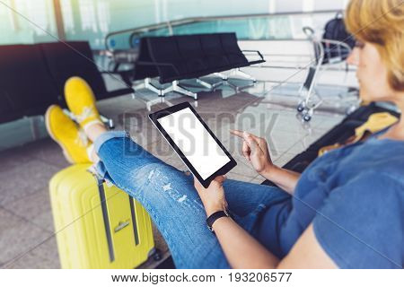 Young hipster girl sitting at airport in yellow boot on suitcase traveling in Europe female hands texting message on gadget in terminal area hall summer journey trip concept mockup blank screen tablet