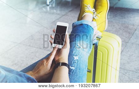 Young hipster girl sitting at airport in yellow boot on suitcase traveling in Europe female hands texting message on gadget in terminal area hall traveler journey trip concept mockup blank screen