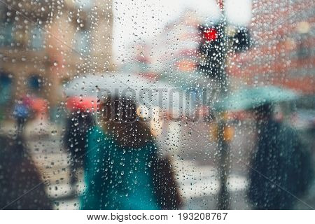 Gloomy day in the city. People in heavy rain. Selective focus on the raindrops. Prague Czech Republic.