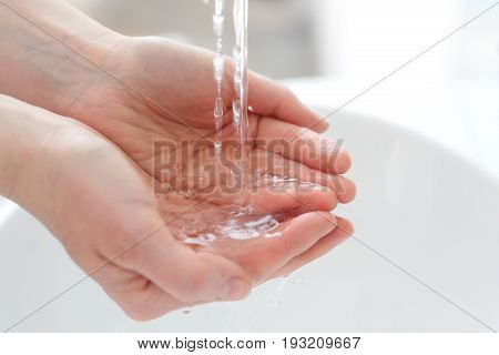 Woman wash her hands under water. Wash your hand.