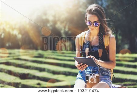 Hipster young girl with bright backpack and vintage camera using tablet or holding gadget planning travel plan. View tourist traveler with sunglasses on background Parc Laberint Barcelona. Mock up for text message