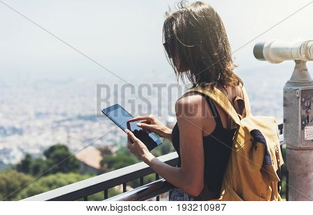 Hipster young girl with bright backpack planning travel plan. View from the back of the tourist traveler on background panoramic view of the city coin operated binoculars. Mock up for text message. Barcelona Tibidabo. Female hands using tablet holding gad