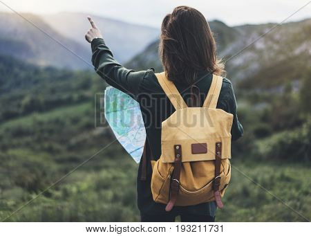 Hipster young girl with bright backpack enjoying sunset on peak of foggy mountain looking a map and poining hand. Tourist traveler on background valley landscape panoramic view mockup sunlight in trip in northern spain basque country mock up for text.