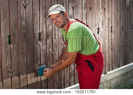 Worker using electric sander to remove old paint from a fence