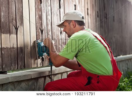 Worker removing old paint from fence using an electric hand tool