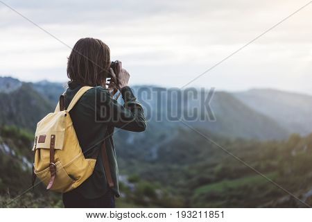 Hipster young girl with bright backpack taking photo of amazing landscape sunset on vintage camera on peak of foggy mountain mockup. Tourist traveler on background sunlight in trip in northern spain basque country mock up for text.