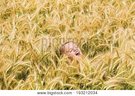 Girl shouting in the wheat field - barely rising above the spikes