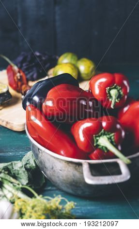 Red and black pepper in a metal bowl on wooden background and yellow tomatoes with basil and spices on a cutting board a healthy natural food closeup