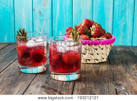 Cocktail-mocktail. Fruity cocktail drink decorated with frozen or fresh raspberry strawberry rosemary ice and soda. Domestic cocktail with ice and rosemary.