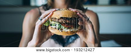 Young girl holding in female hands fast food burger american unhealthy calories meal on blue background mockup with copy space for text message or design hungry human with grilled hamburger front view