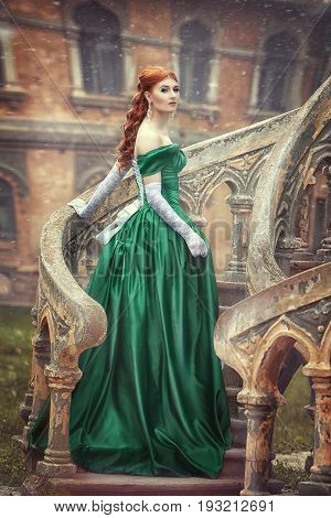 Beautiful, young, red-haired girl in a green medieval dress, In white gloves, Climbs the stairs to the castle. Fantastic photosession.