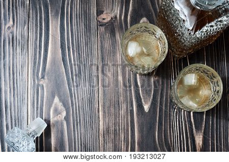 Glass of whiskey with ice cubes and whiskey bottle on an old wooden table with copyspace