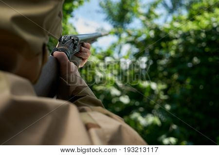 Duck hunter aiming his shotgun. Hunter in camouflage jacket on hunting in anticipation of prey.