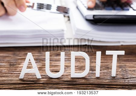 Close-up Of White Audit Text In Front Of Auditor Calculating Invoice