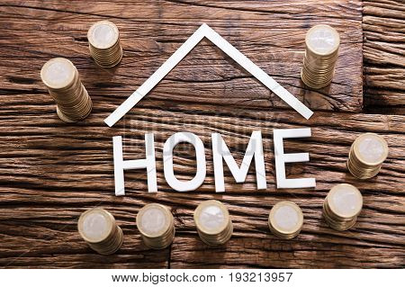 High Angle View Of Home Word With Stacked Coins On Wooden Background