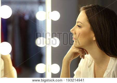 Side view of a serious woman looking at make up mirror