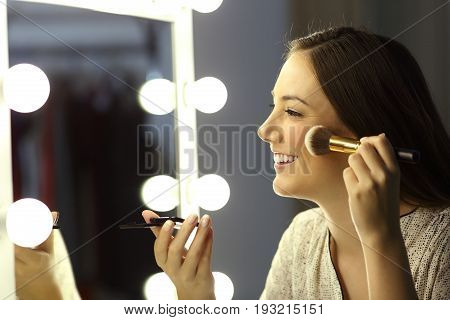 Profile of a woman making up using a brush in front of a make up mirror