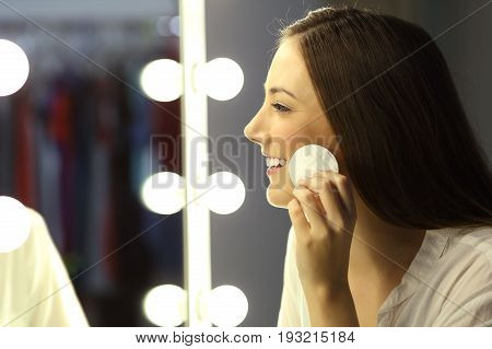 Side view of a woman removing make up with a remover in front of a mirror