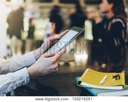 Closeup of a woman pointing finger to an blank display of the tablet with a blue color in a homelike atmosphere on warm bokeh background lighting color female hends using computer in cafe with reflection and glare