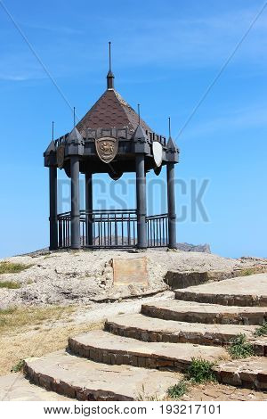 The steps leading to the gazebo on a cliff in the town of Sudak on a summer sky background.