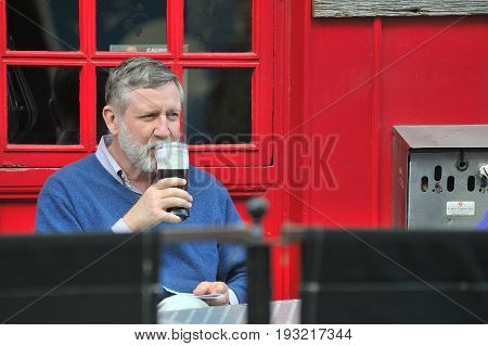 Galway City Center, Ireland June 2017,man Drinking A Pint Of Guiness In A Bar Terrace