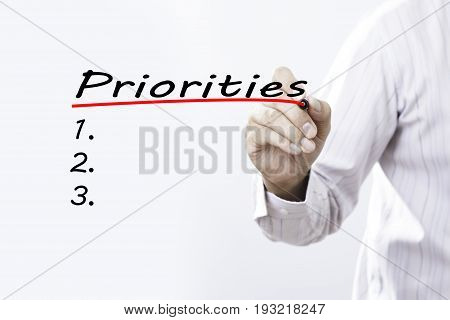 Businessman hand writing Priorities with red marker on transparent wipe board business concept