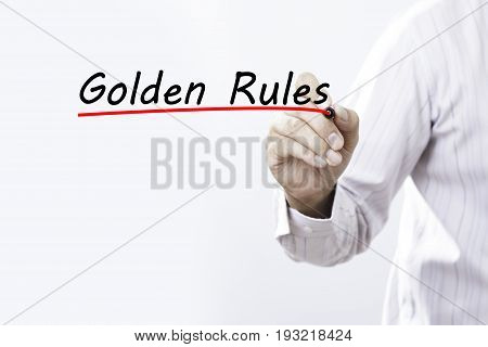 Businessman hand writing Golden Rules with red marker on transparent wipe board business concept