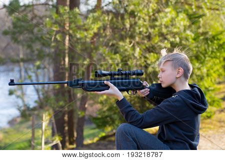 teenager with air gun in the forest