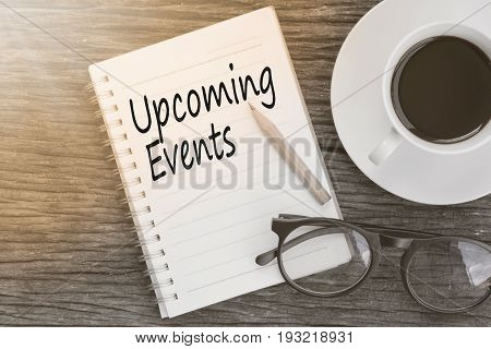 Concept Upcoming Events message on notebook with glasses pencil and coffee cup on wooden table.
