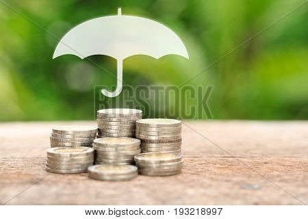 Coverage insurance or Protection concept Stacks and heaps of coins umbrella nature background