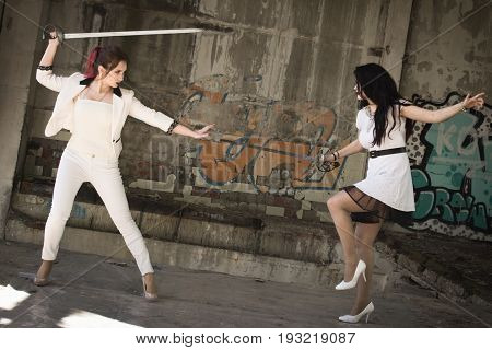 Two Businesswomen Are Fighting At Swords.