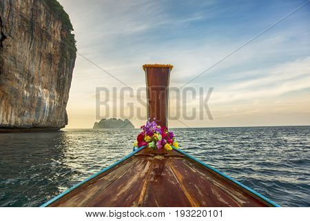 Traditional longtail boat at sunset on tropical island Thailand