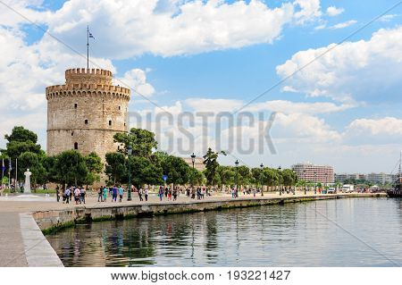 Thesalloniki, Macedonia, Greece - 12th May 2015: People walking and relaxing near white Tower, Thessaloniki, Greece. This tower is a monument and museum on the waterfront of the city.