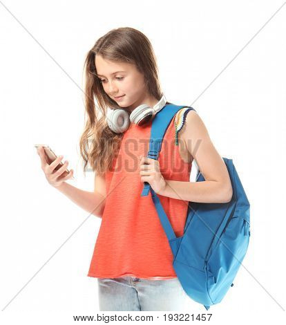Cute teenager girl with mobile phone, headphones and schoolbag on white background
