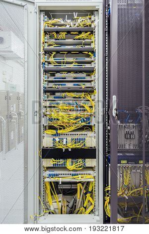 Inside the cabinet with switchboard and other telecommunication mobile network equipment with many cables