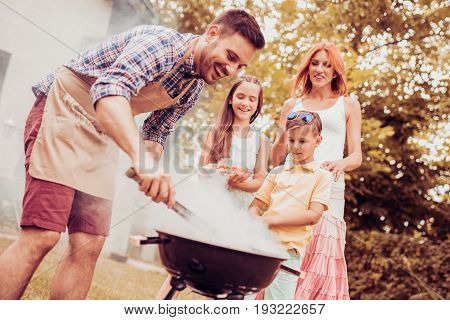Happy family having a barbecue in their garden in summer.Leisure food family and holidays concept.