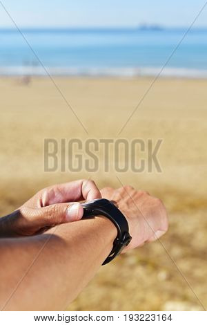 closeup of a young sportsman syncing his smartwatch, with the sea in the background and a large blank space above him