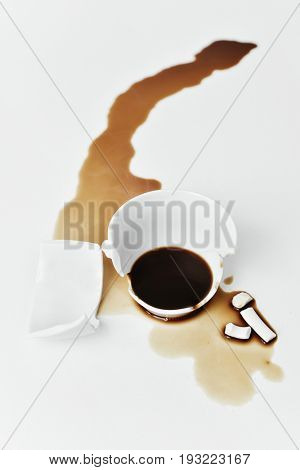 a broken white ceramic cup of coffee with its pieces and the coffee spilled on a white table