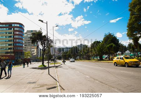 QUITO, ECUADOR - MAY 06 2016: Unidentified people walking in the mainstreet in NNUU avenue with some buildings, cars and people in the city of Quito.