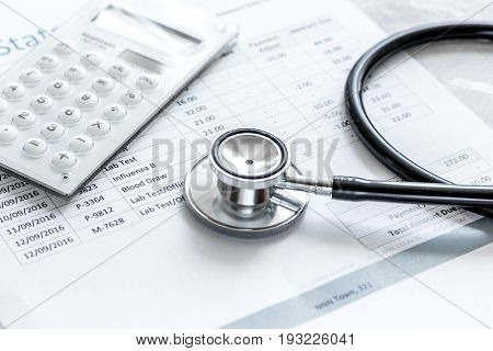 health care costs with billing statement, stethoscope and calculator on stone table background
