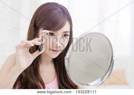 woman take clip eyelashes on the blue background