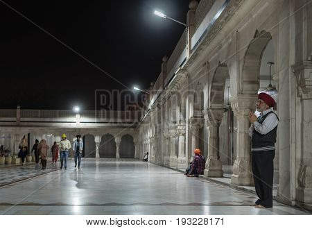 The elderly Sikh makes a prayer in the yard of the temple of Gurudwara Bangla Sahib against the background of gallery of surrounding Sarowar pond. On March 14 2017 New-Delhi India.