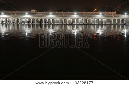 Night view of gallery of one of the main Sikh shrines - the temple of Gurudwara Bangla Sahib. The construction in night illumination is reflected in Sarowar pond water.